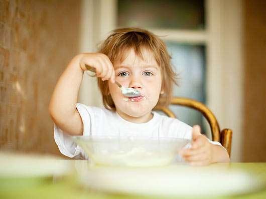 niña comiendo con cuchara